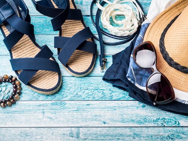 Sfondo estivo cappello di paglia bracciali sandali occhiali da sole seashells su un tavolo blu