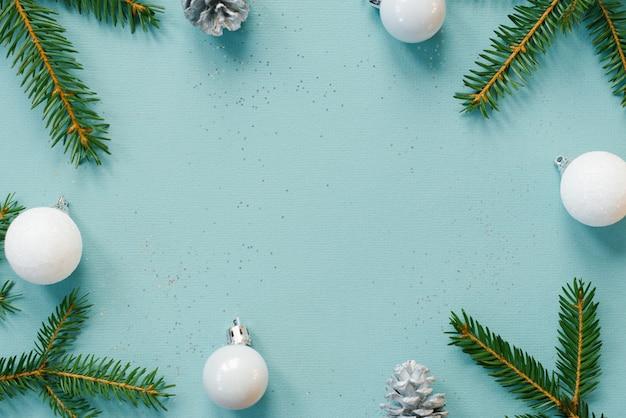 Sfondo festivo di natale o capodanno con rami di abete rosso, paillettes, coni e giocattoli dell'albero di natale bianco sulla superficie della carta di menta