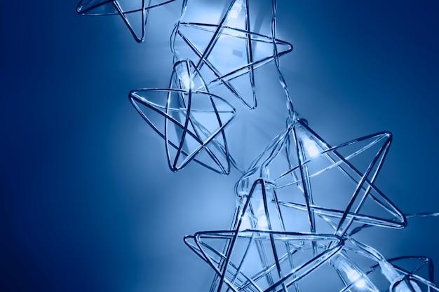Sfondo festivo fatto di luci a forma di stelle al neon su oscurità. concetto di partito. classico colore blu dell'anno 2020. tempo di natale. sfondo perfetto per il nuovo anno. copia spazio, disteso
