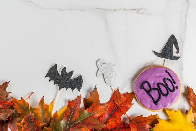 Sfondo festivo per halloween, tavolo in marmo bianco con biscotto di pan di zenzero con la scritta boo !, simboli di festa (pipistrello, cappello da strega, fantasma) e foglie gialle rosse autunnali, vista dall'alto copia spazio cornice