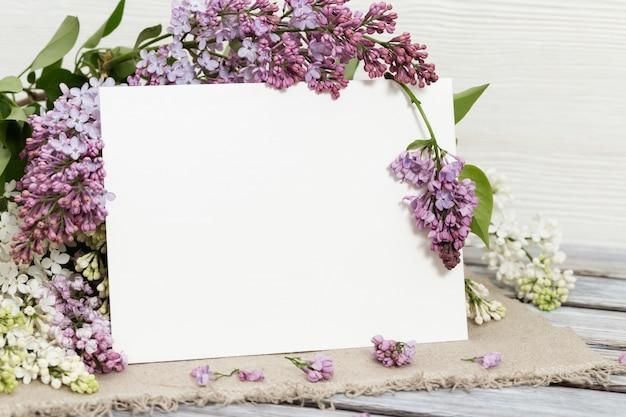 Sfondo floreale con fiori lilla e lista di carta per le congratulazioni. cartolina festiva. copia spazio per il testo.