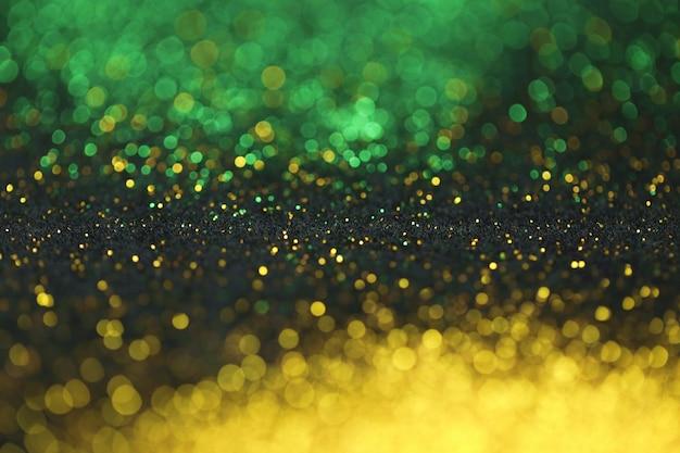 Sfondo glitter oro e verde con brillante bokeh