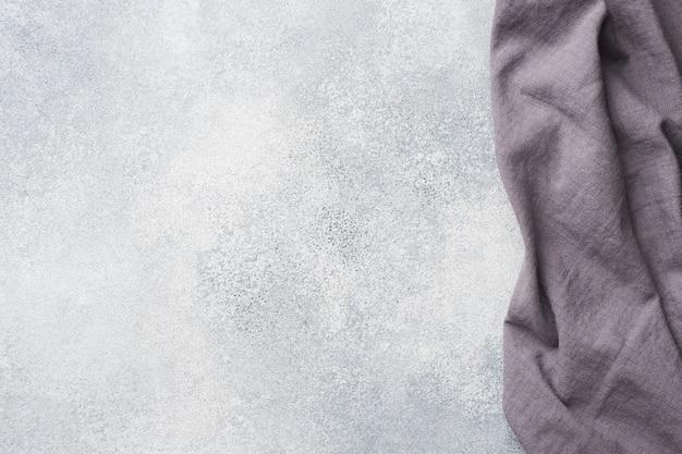Sfondo grigio cemento con tovagliolo viola. vista dall'alto.