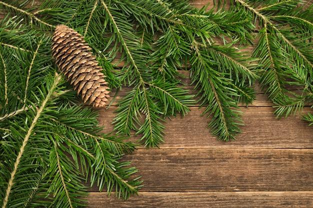 Sfondo in legno con rami di abete e coni nell'angolo del telaio