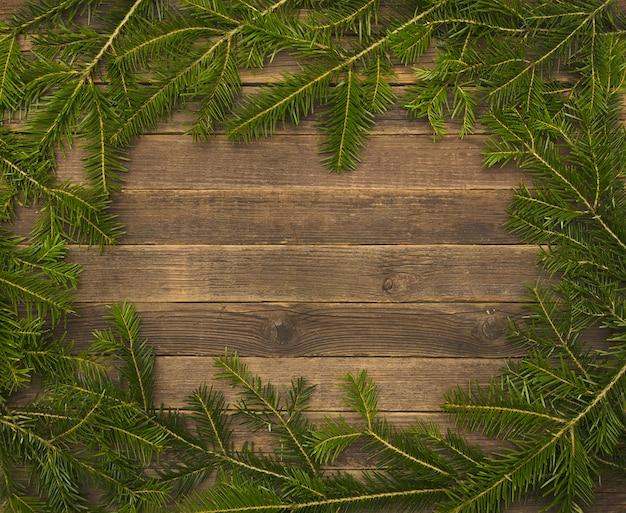 Sfondo in legno con rami di abete sul bordo.