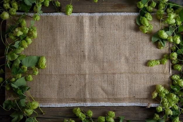 Sfondo in legno vecchio tavolo o pavimento in legno. luppolo. tela di sacco.