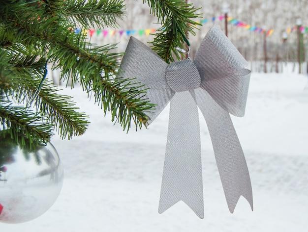 Sfondo invernale con albero di natale, palline, fiocco d'argento, buon natale e capodanno.