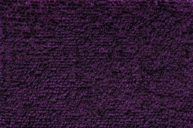 Sfondo lanuginoso viola scuro di soffice panno morbido. trama del primo piano della tessile