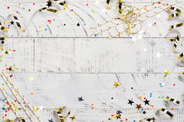 Sfondo luminoso festivo di carnevale con cappelli, stelle filanti, coriandoli e palloncini su sfondo bianco