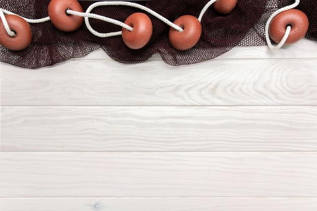 Sfondo marino con tavolo in legno e reti da pesca