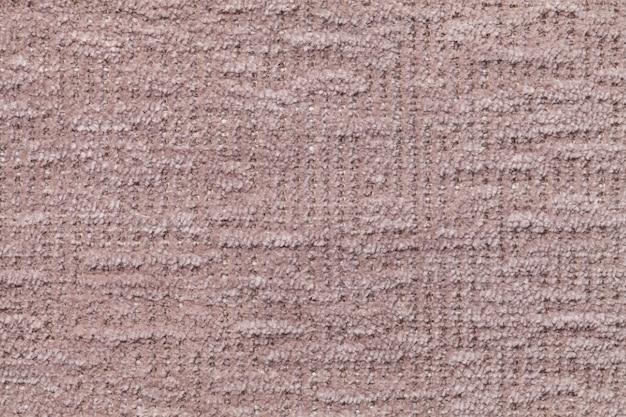 Sfondo marrone chiaro soffice di panno morbido e soffice. struttura del tessuto simile a pelliccia della peluche, primo piano.