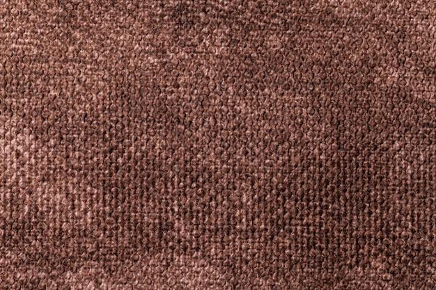 Sfondo marrone scuro da materiale tessile morbido. tessuto con trama naturale.