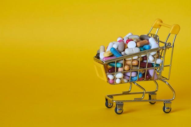 Sfondo medico o concetto. il primo piano di un carrello della spesa ha riempito di pillole variopinte. carrello dal supermercato con diverse medicine.