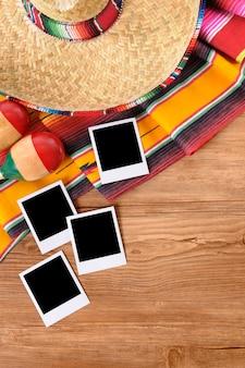 Sfondo messicano con stampe di foto in bianco su un tavolo di legno di pino