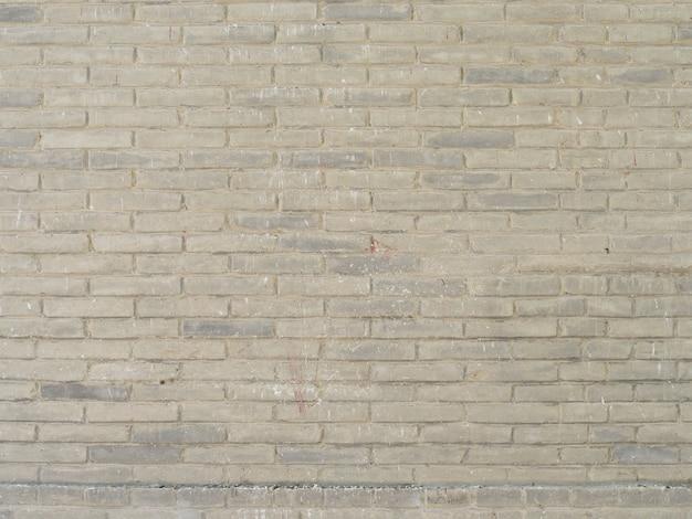 Sfondo muro di mattoni con blocchi grigi.