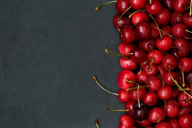 Sfondo nero con ciliegie dolci mature
