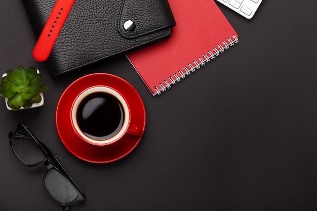 Sfondo nero con tazza di caffè rosso, blocco note, sveglia e fiori in vista dall'alto