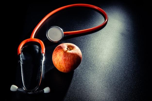 Sfondo nero con una mela e uno stetoscopio
