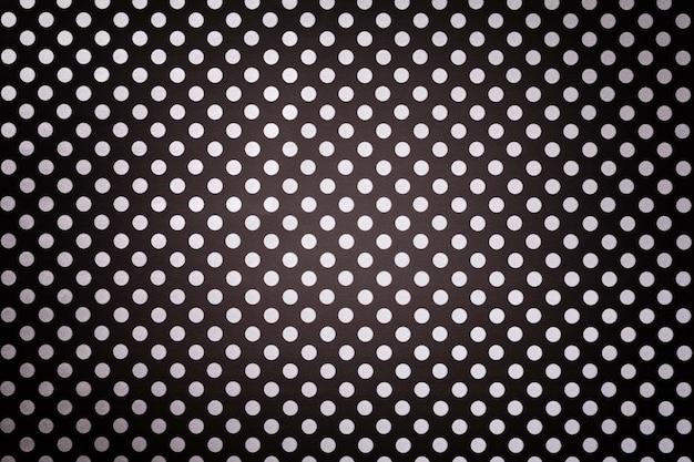 Sfondo nero da carta da imballaggio con un modello di primo piano bianco a pois.