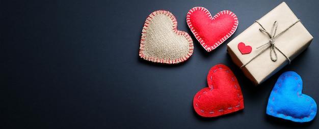 Sfondo o banner di cuori rossi e blu o di san valentino, su sfondo nero. un regalo per le vacanze di san valentino, fatto a mano.