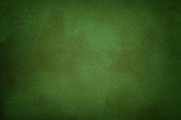 Sfondo opaco verde scuro del tessuto scamosciato, primo piano.