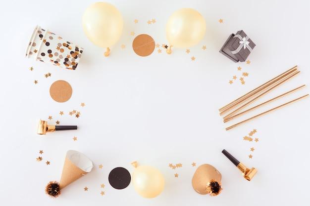Sfondo oro festa, carnevale, festival e compleanno con palloncino, stelle filanti colorate e coriandoli. vista dall'alto e laici piatta del bordo su uno sfondo bianco con spazio di copia