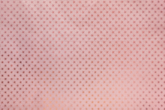 Sfondo oro rosa da carta stagnola con un motivo a stelle
