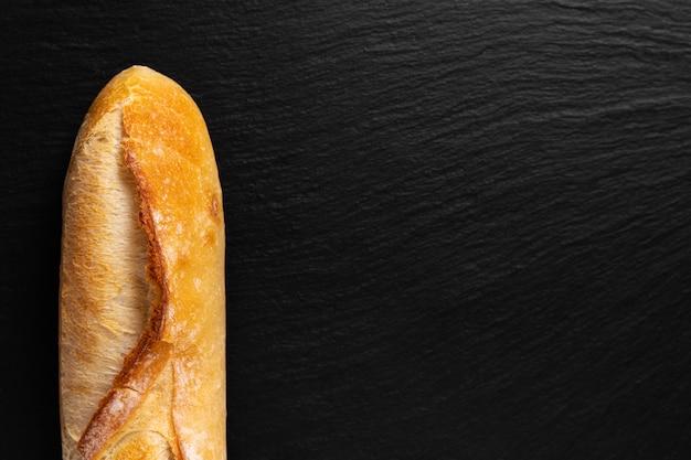 Sfondo per la presentazione di cibo baguette francese sul bordo di ardesia nera con spazio di copia