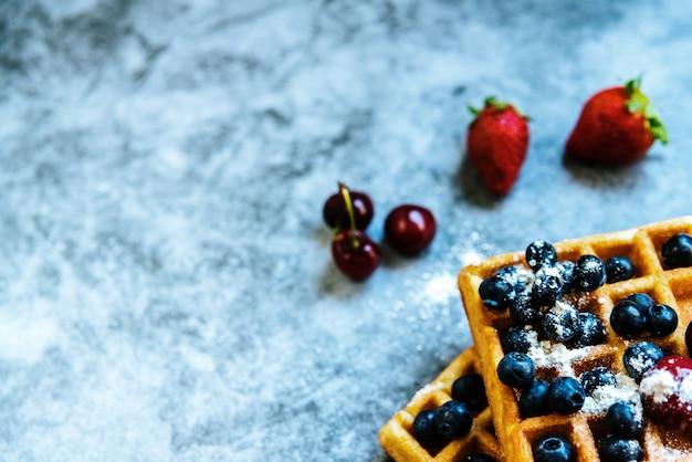 Sfondo pulito con spazio negativo per cibi sani e frutti antiossidanti e un waffle come cibo spazzatura.