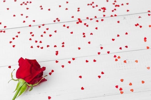 Sfondo romantico con rosa rossa sul tavolo di legno
