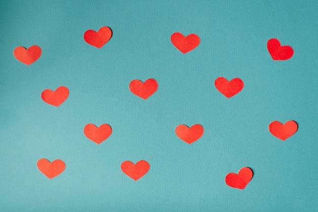 Sfondo romantico di san valentino, simpatici cuori piatti laici, design minimalista banner wallpaper. cuori rossi tagliati cuori su sfondo blu
