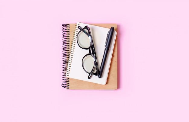 Sfondo rosa con blocco note, occhiali da ufficio, penna, posto per il testo. concetto di tendenza.