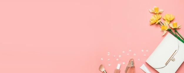 Sfondo rosa con borsa estiva bianca, fiori gialli, profumo, smalto per unghie