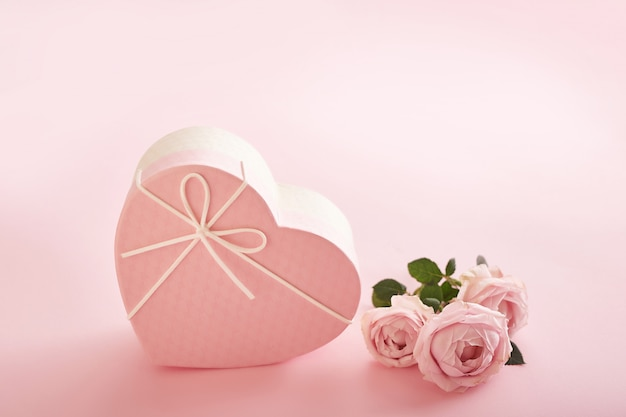 Sfondo rosa con fiori e scatola regalo