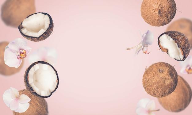 Sfondo rosa estate tropicale con noci di cocco che cadono