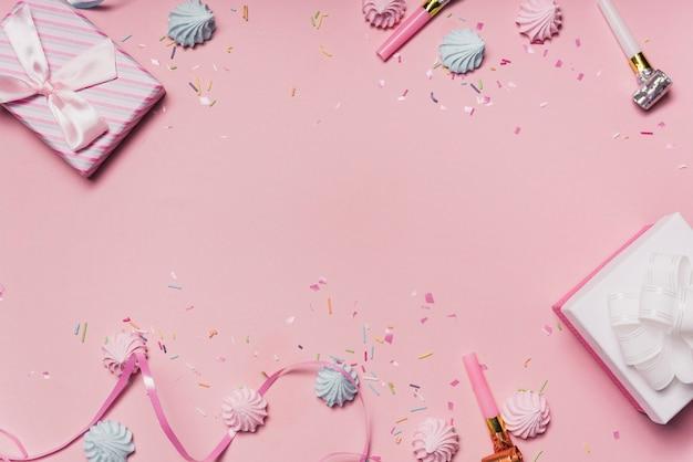 Sfondo rosa festa con caramelle; soffiatori di partito e nastro arricciato