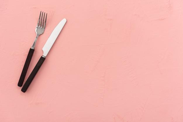Sfondo rosa pastello con cibo coltello e cucchiaio