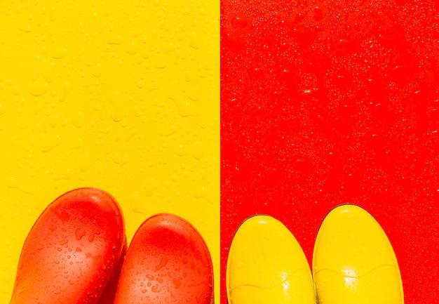 Sfondo rosso bagnato con stivali di gomma gialli