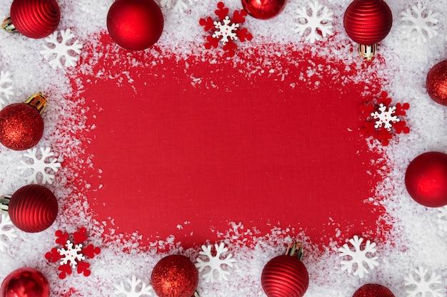 Sfondo rosso di natale con neve, fiocchi di neve e palline. inverno, festività.