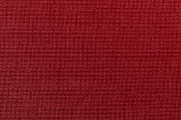 Sfondo rosso scuro da un materiale tessile. tessuto con trama naturale. scenografia.
