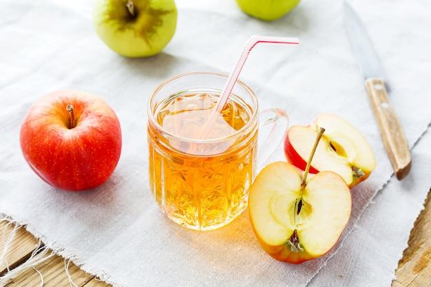 Sfondo rustico con mele e succo di mela in vetro