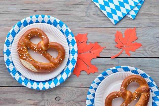 Sfondo rustico oktoberfest con prezels in piatti di carta