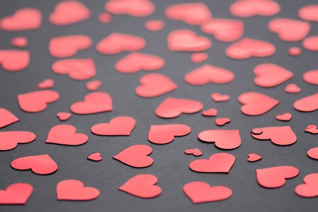 Sfondo scuro con coriandoli cuori rossi per san valentino