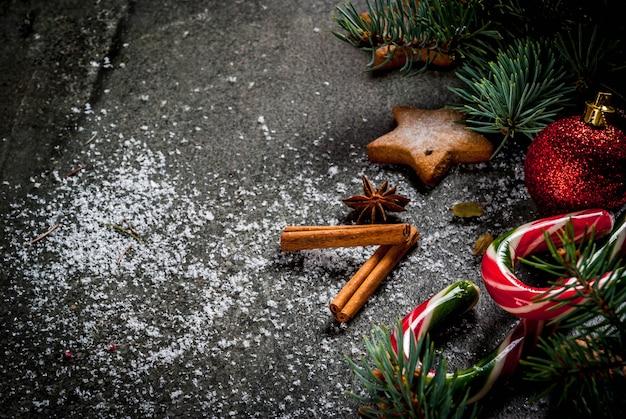 Sfondo scuro di natale con rami di albero di natale, pigne, dolci di canna di caramella, regali, palle di natale e decorazioni