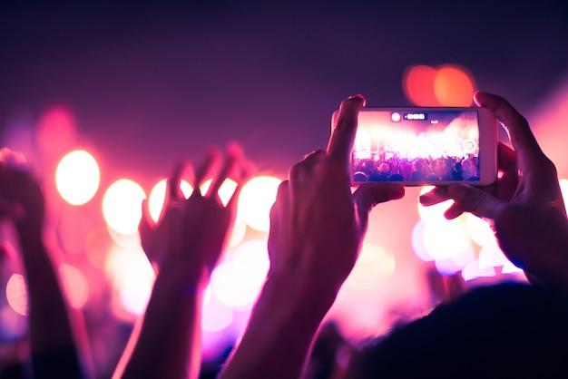 Sfondo sfocato colorato della mano che tiene smart phone per scattare foto persone ammassate in concerto.