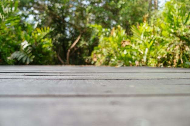 Sfondo sfocato del pavimento in legno con foresta lussureggiante.
