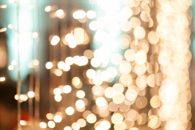 Sfondo sfocato di molte piccole decorazioni di lampadina nella festa di notte.