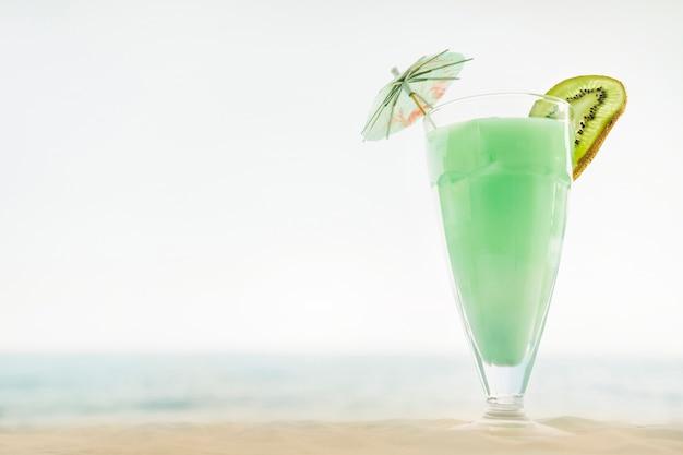 Sfondo spiaggia con cocktail di kiwi