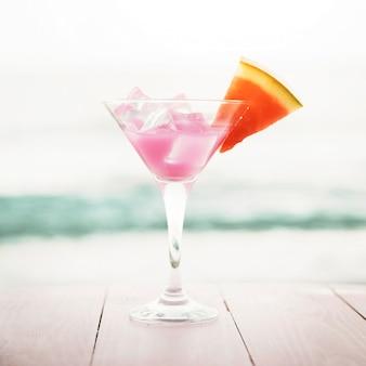 Sfondo spiaggia con cocktail rosa e anguria