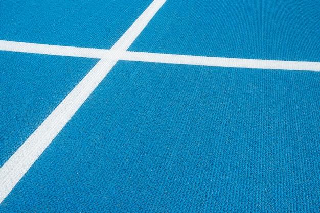 Sfondo sportivo pista corrente blu con le linee bianche nello stadio di sport. vista dall'alto
